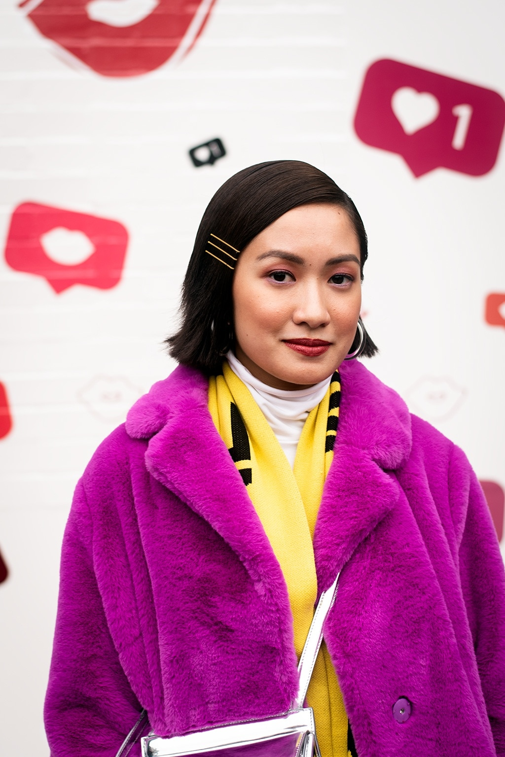 NYFW AW19 Street Style: Shot of woman with dark brown sleek bob haircut with bobby pins, wearing neon pink jumper with neon yellow top