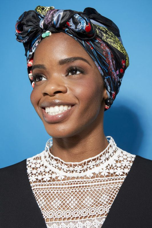 Perm rods on natural hair video step 4: Close up shot a model with natural hair wrapped up in a silk scarf posing in a studio setting