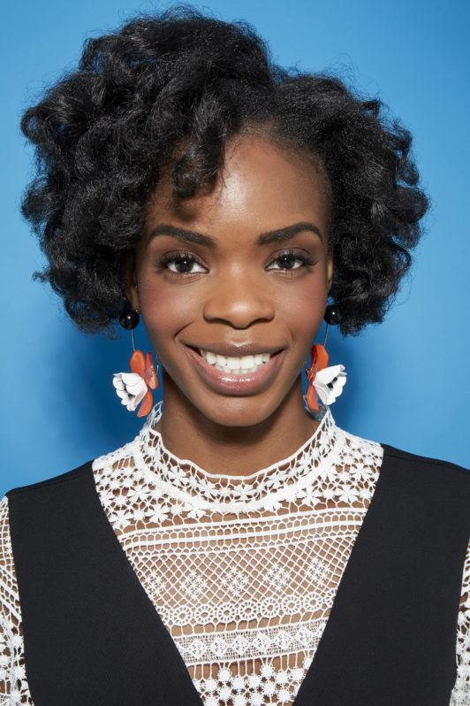 Perm rods on natural hair video step 8: Close up shot of woman with medium dark brown curls smiling in a studio setting