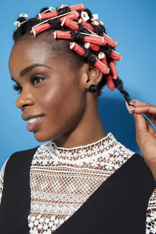 Perm rods on natural hair video step 5: Close up shot of a woman with natural in perm rods, removing one perm rod while posing in a studio setting