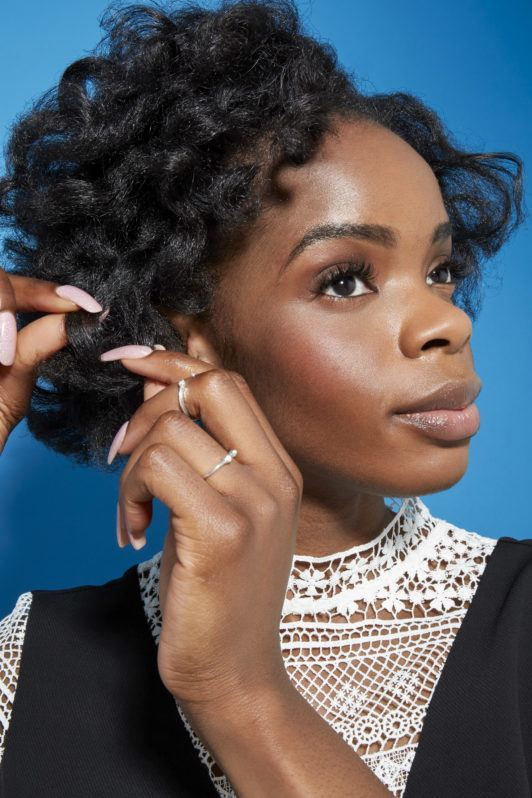 Perm rods on natural hair video step 6: Close up shot of woman touching her medium natural dark brown curls in a studio setting