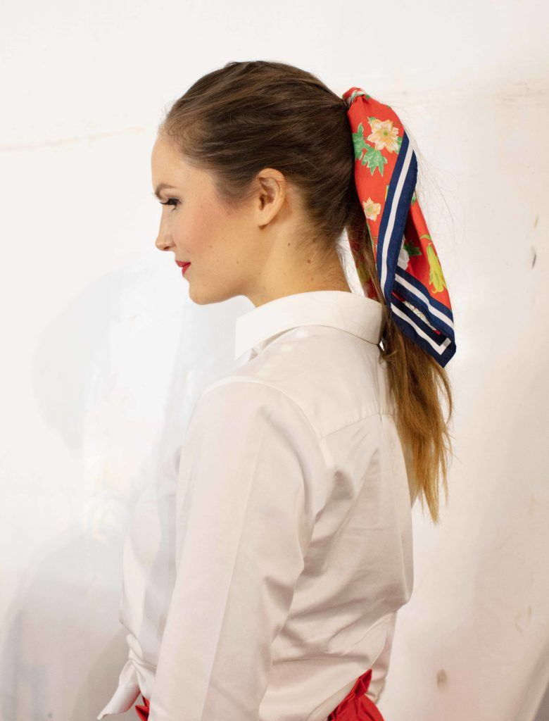 Vintage hairstyles for long hair: Close up shot of a woman with long medium dark brown hair styled into a retro pony with a scarf tied around it at Goodwood festival