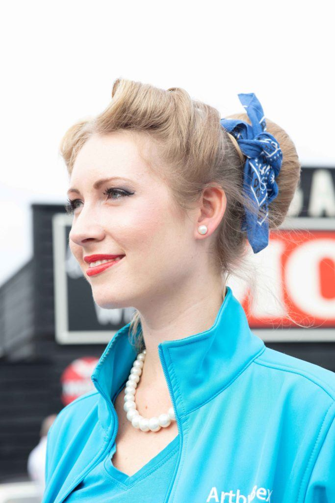 Retro hairstyles: Close up shot of a woman with natural blonde hair styled into a victory rolls bun updo, wearing blue at the Goodwood festival