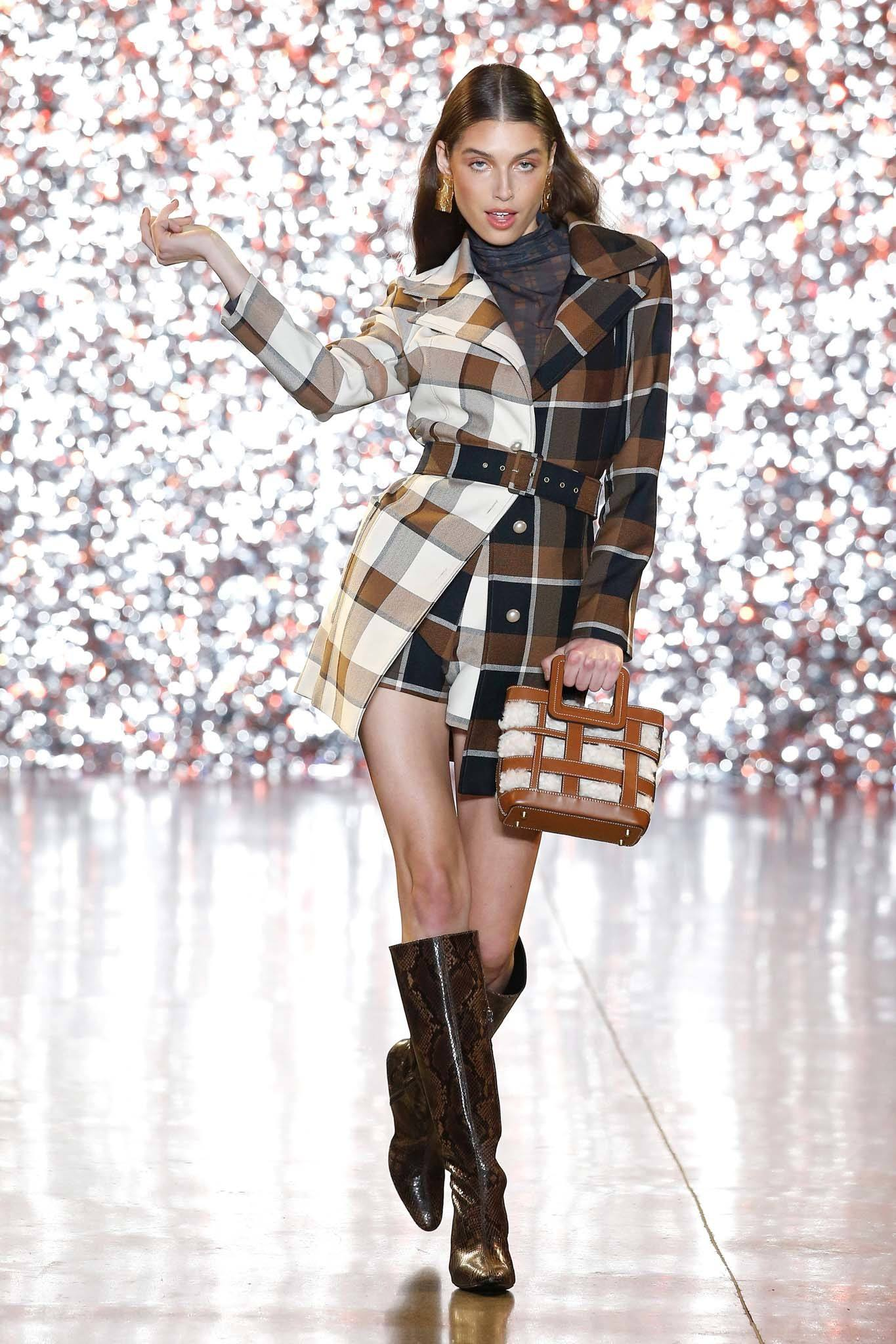 NYFW Catwalk Trends: Model on Staud FW19 runway with long straight brown hair tucked behind her ears with a wet look finish wearing a check trench coat.