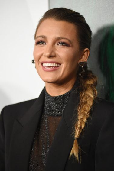 Winter hairstyles 2018: Blake Lively with her dark blonde hair in a textured side braid, wearing a black blazer and sheer black high neck top