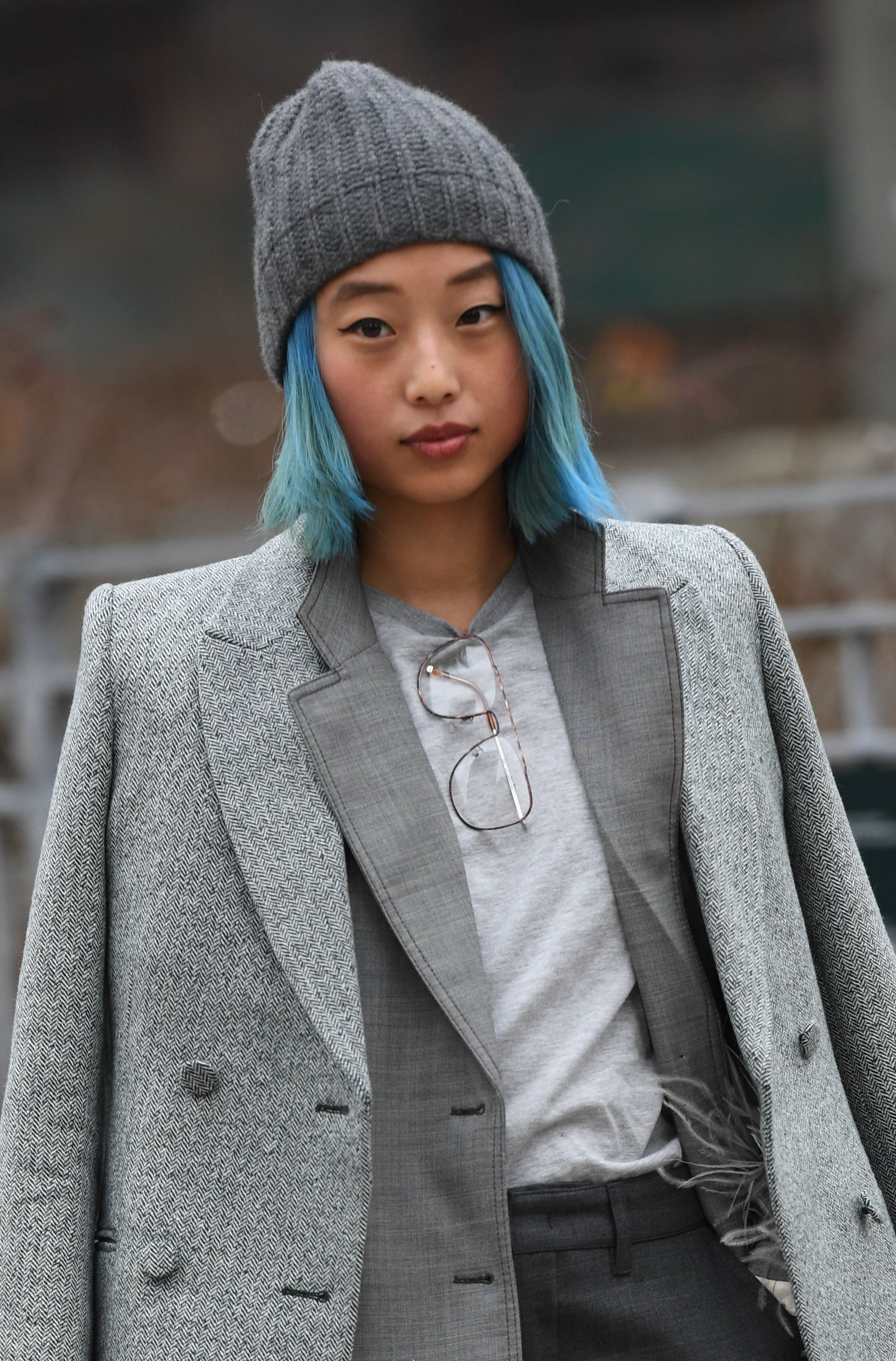 2019 hair colour trends: Street style shot of a woman with a blue bob, wearing a grey beanie and a grey outfit