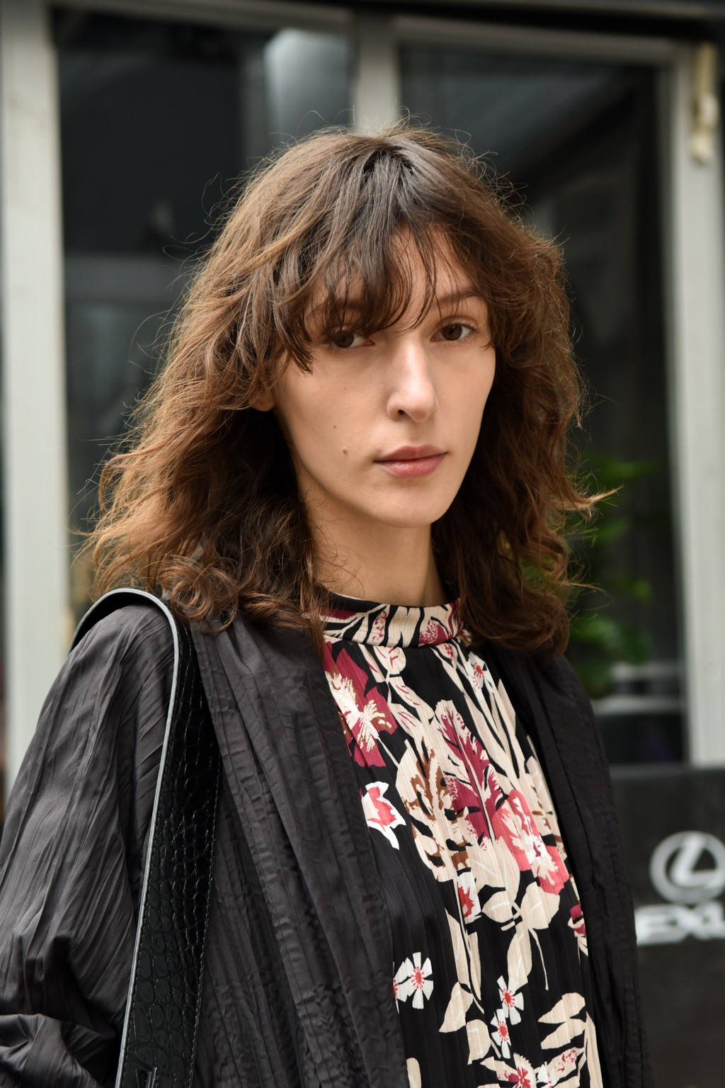Hair treatment guide: Woman with medium brown shaggy hair with fringe, wearing leather jacket and floral top