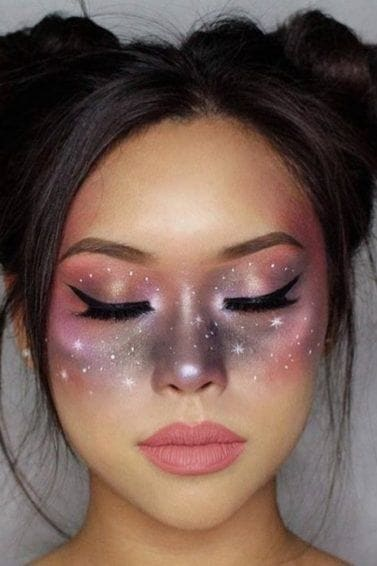 Halloween hairstyles: Woman with dark chocolate hair styled into romantic space buns, with galaxy makeup on her face, posing in a studio setting