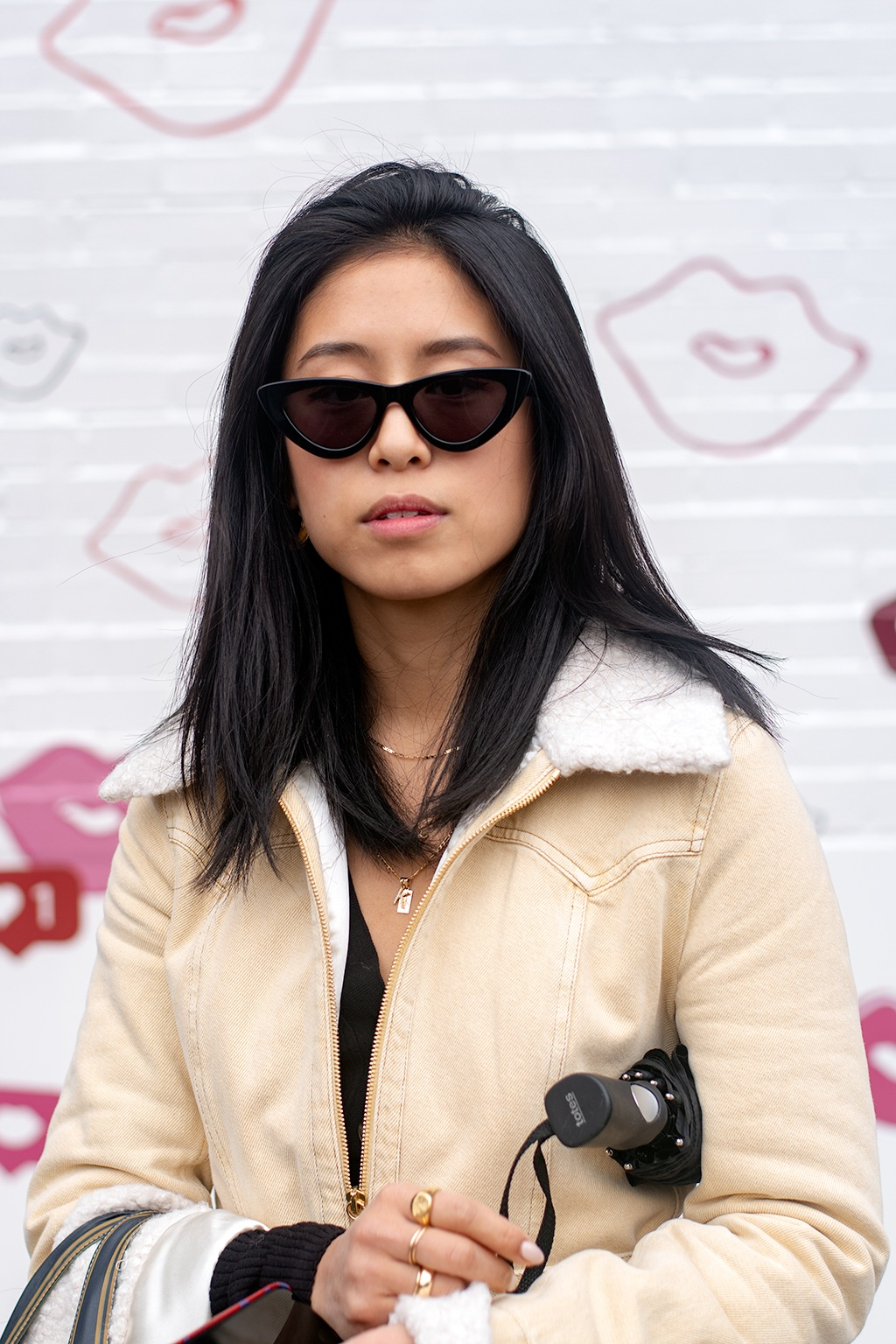 2019 hair colour trends: Street style shot of a woman with shoulder length jet black hair, wearing black retro cat eye sunglasses and a beige jacket