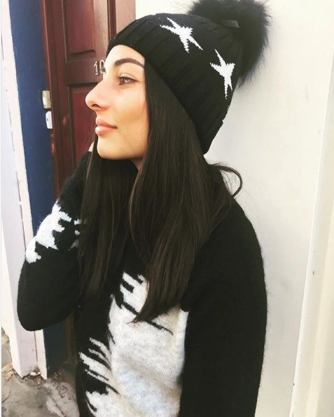 Woman with dark brown long straight hair wearing a pom pom bobble hat and winter jumper