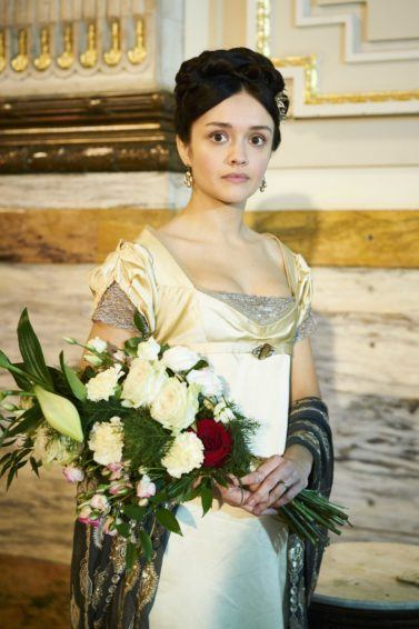 Victorian hairstyles: Still from ITV's Vanity Fair of actress Olivia Cooke as Becky Sharp with her hair in a pinned updo with a flower accessory, wearing Victorian period dress and holding a bouquet