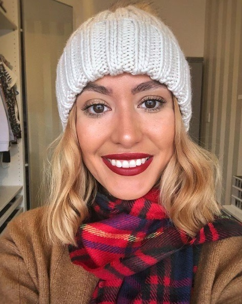 Selfie of a woman with honey blonde wavy bob hair, wearing a white knitted bobble hat, red tartan scarf and a camel coat