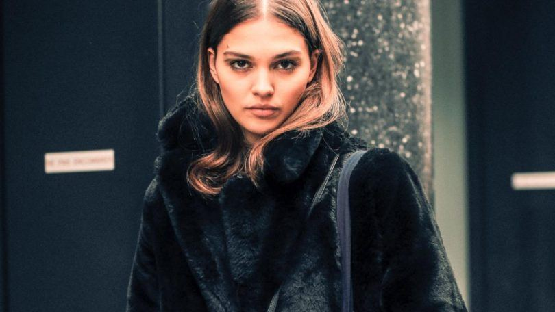 Winter hair mask guide: Street shot of young woman with chestnut brown hair tucked into a big, black fake fur jacket, wearing a tote black and a cross body handbag while posing