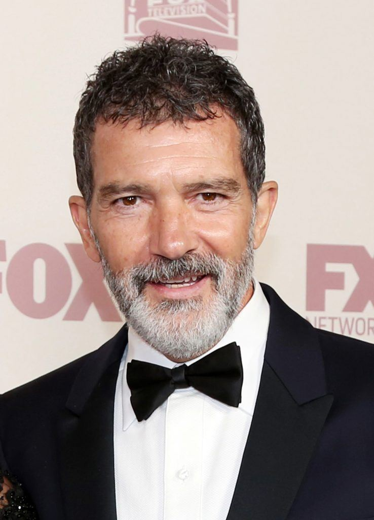 Hairstyles for men over 50: Antonio Banderas with brown French crop hairstyle with salt and pepper grey beard wearing a smart suit.