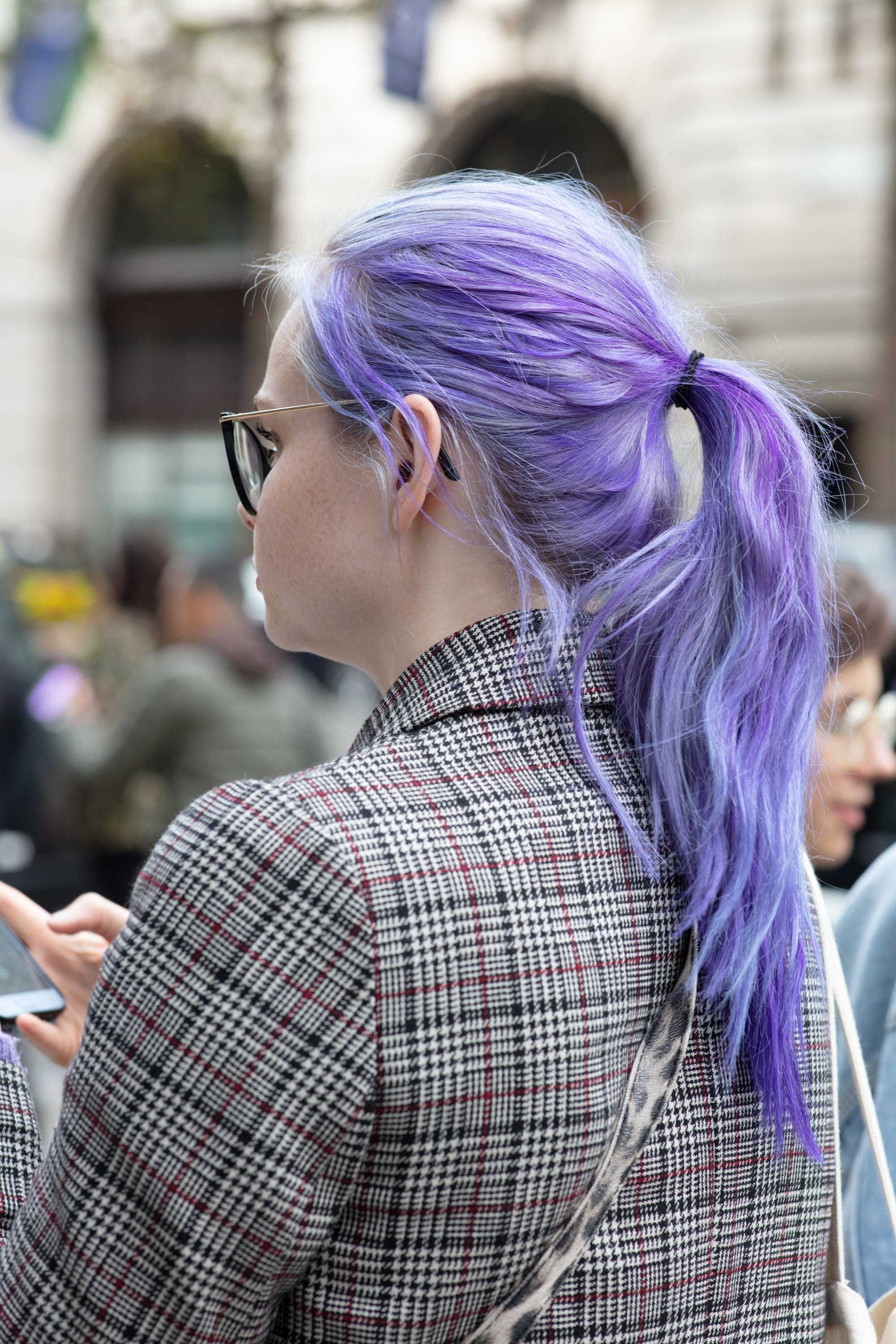 Best shampoo for coloured hair: Backshot of woman with long purple hair styled into a ponytail, wearing a checked blazer and posing on the street for an All Things hair street shot