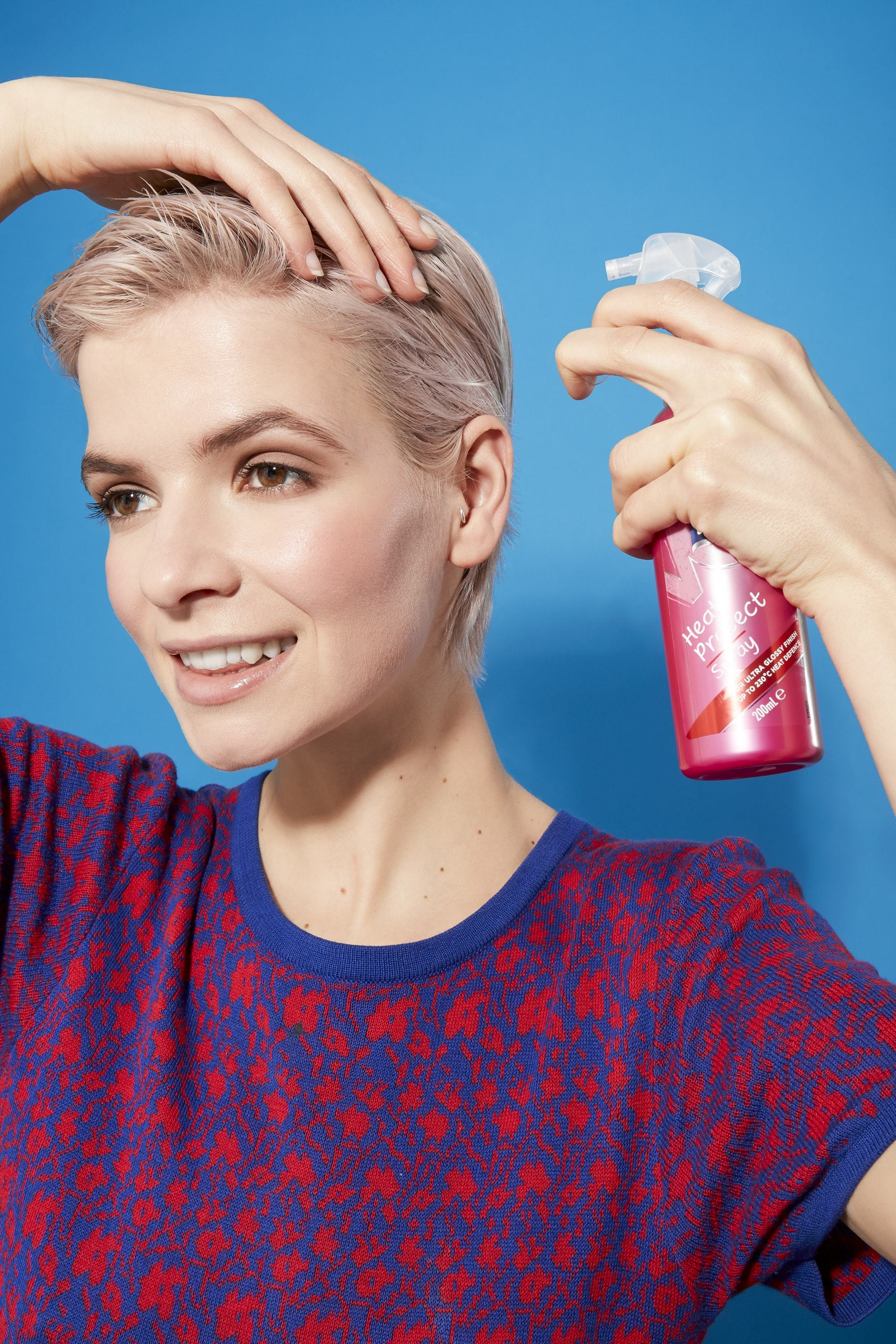 Bleach blonde woman holding her hair and spraying VO5 heat protect spray