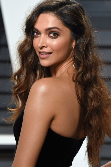 Bollywood hair: Deepika Padukone with long curly brown to caramel brown hair, wearing a black dress on the red carpet