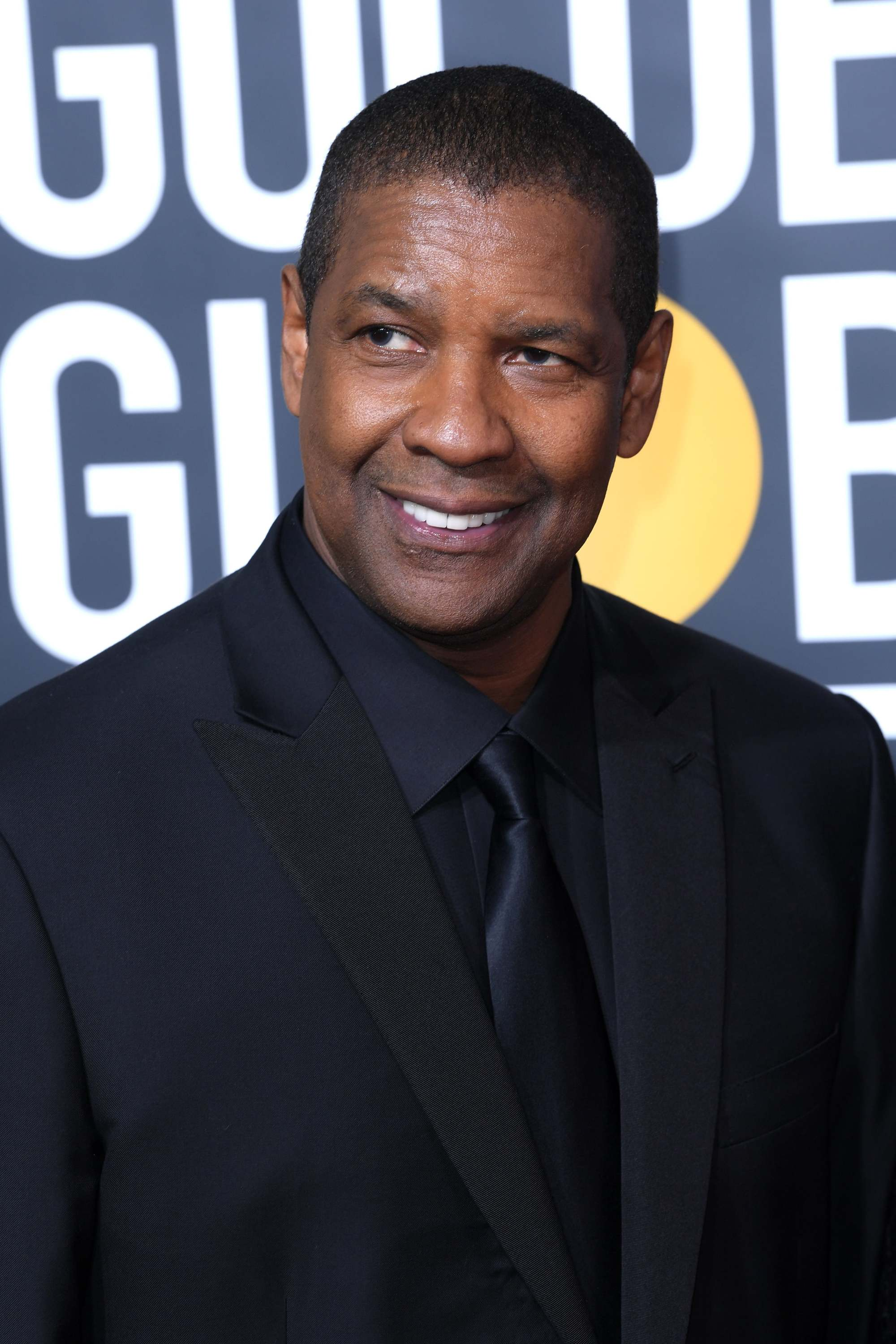 Hairstyles for men over 50: Denzel Washington with short shaved hair wearing a black suit at Golden Globes event.