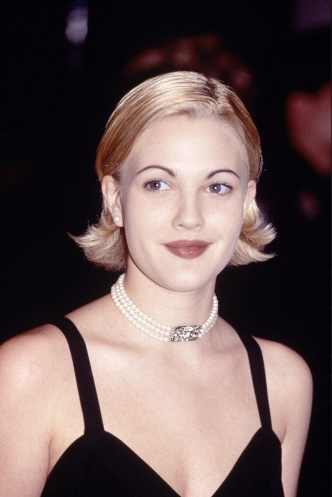 Drew Barrymore with a short blonde bob with flicked out ends wearing a choker and black little black dress.
