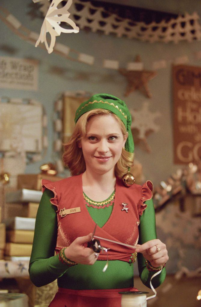 Elf: Zooey Deschanel as Jovie with her medium blonde hair styled into loose curls, wearing a green elf costume and hat with a bell on it, on set
