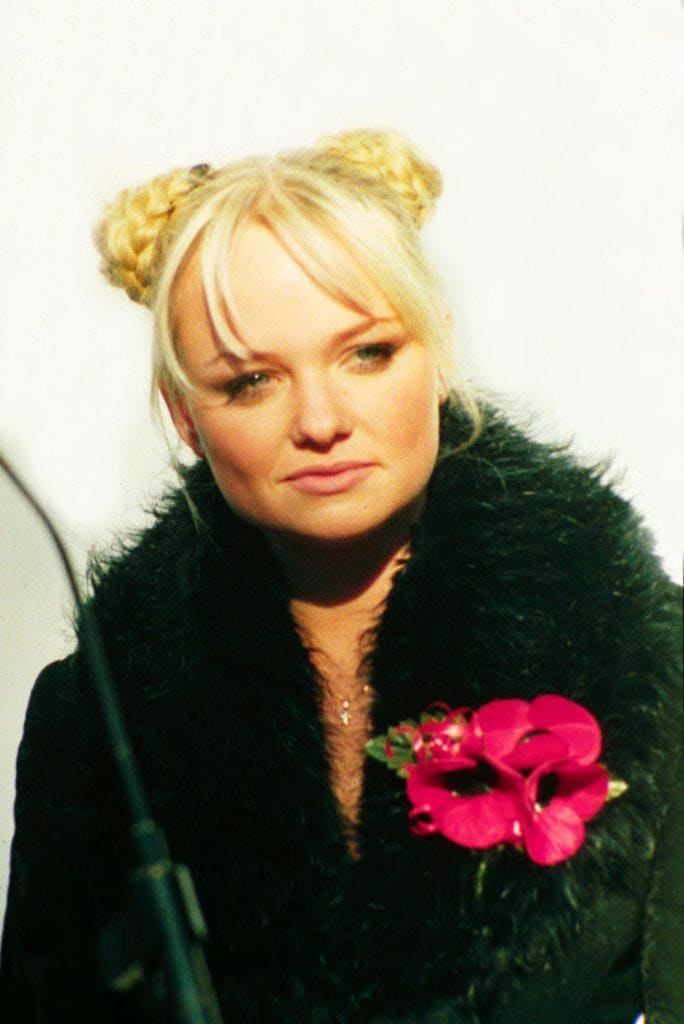 Emma Bunton with blonde hair in braided space buns with parted fringe wearing a black fur jacket.