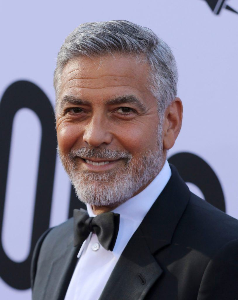 Hairstyles for men over 50: George Clooney with a short tapered combover and grey beard wearing a smart suit.