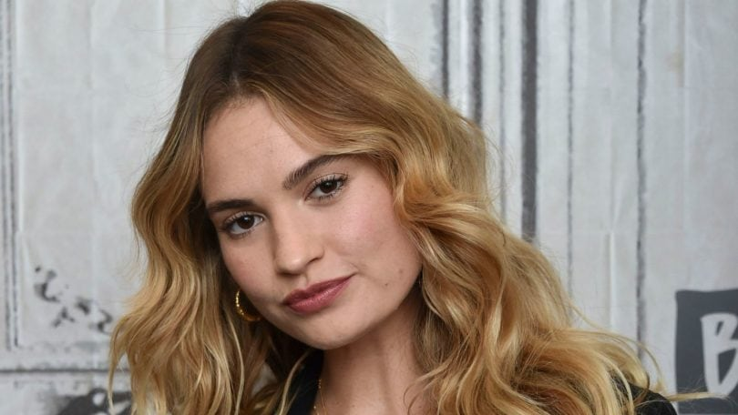 How to use volume spray guide: Lily James with bronde long wavy, voluminous hair, wearing black boiler suit and posing on the red carpet