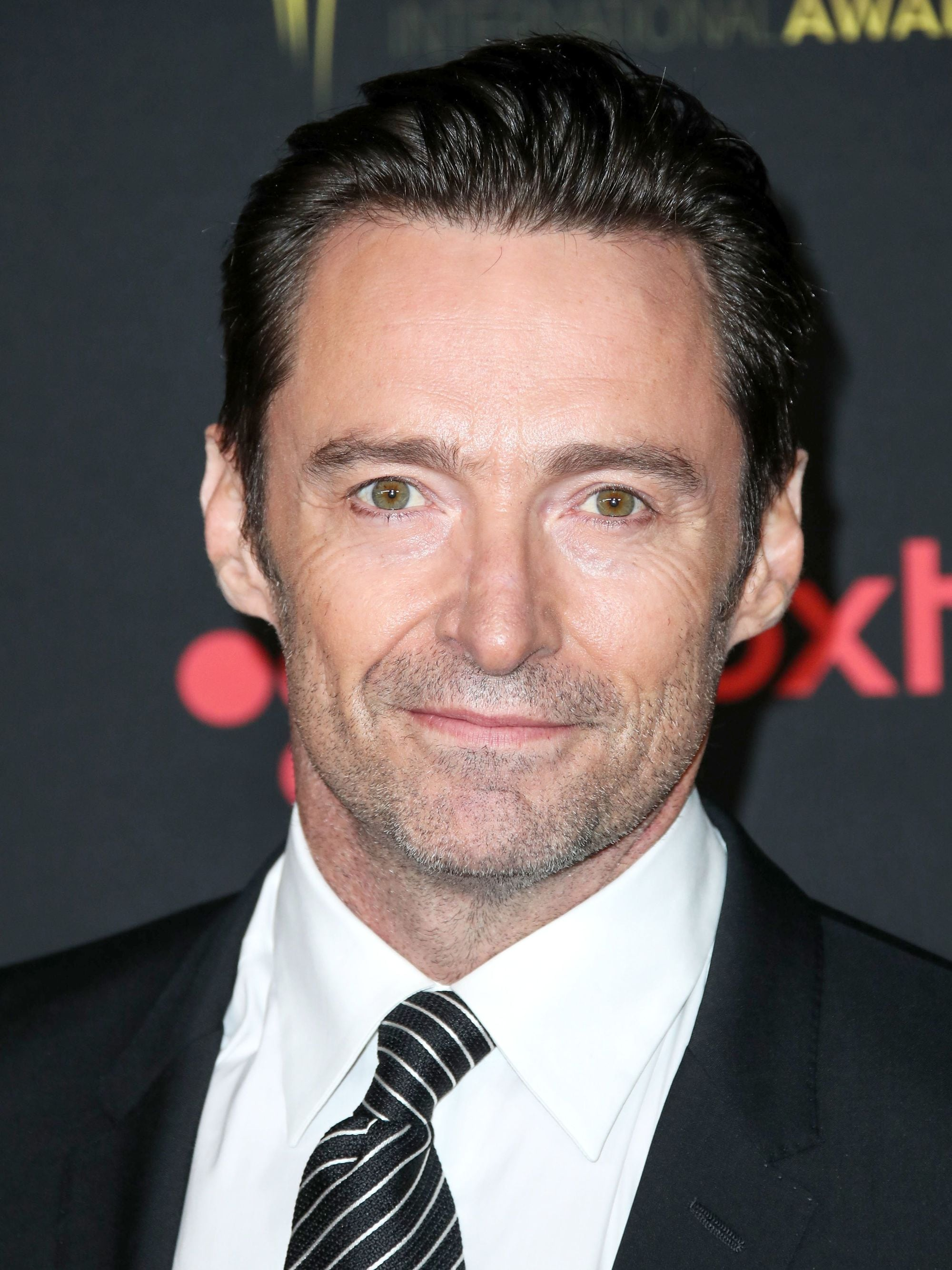 Hairstyles for men over 50: Hugh Jackman with brown swept back short hair wearing a smart suit on the red carpet.