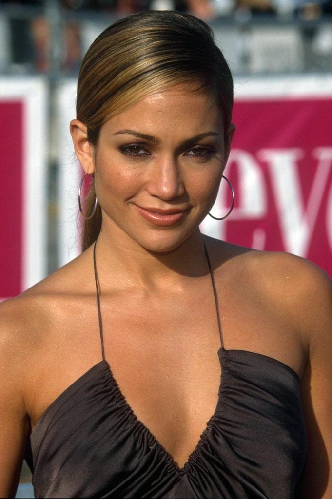 Jennifer Lopez with straight brown highlighted hair in side parted low ponytail updo in the '90s.