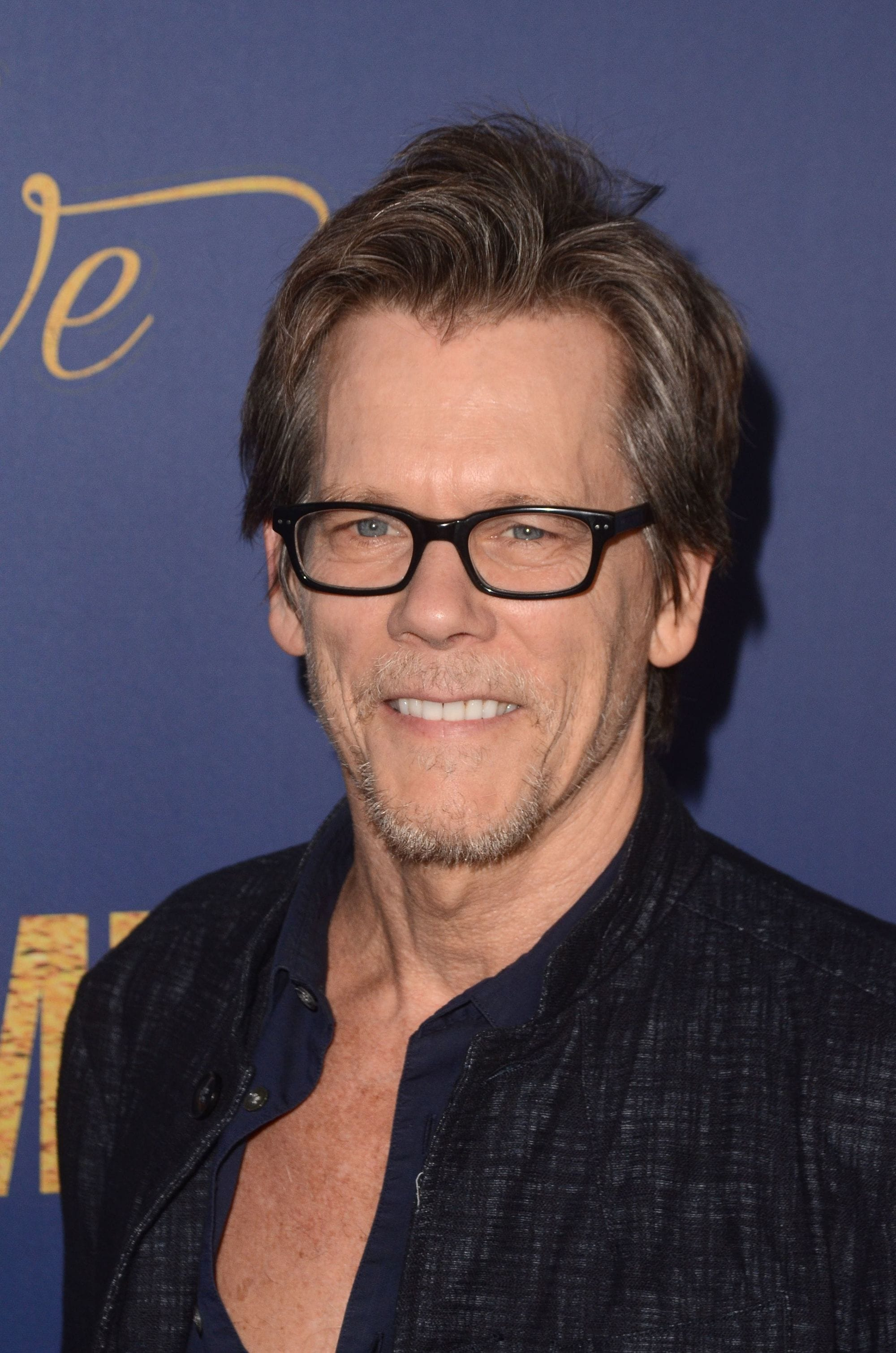 Hairstyles for men over 50: Kevin Bacon with brown straight flow hair wearing black rimmed glasses.