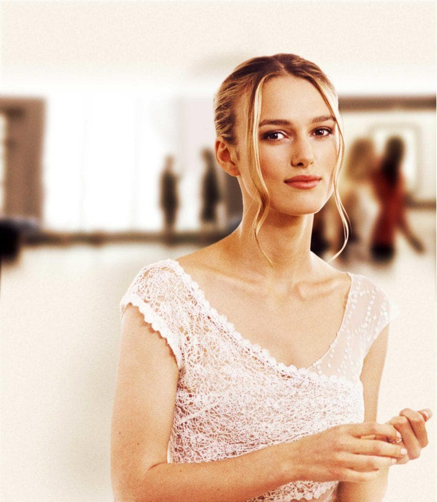 Love Actually: Kiera Knightley as Juliet with a lace wedding dress, with her golden blonde hair styled into romantic updo, posing on the set