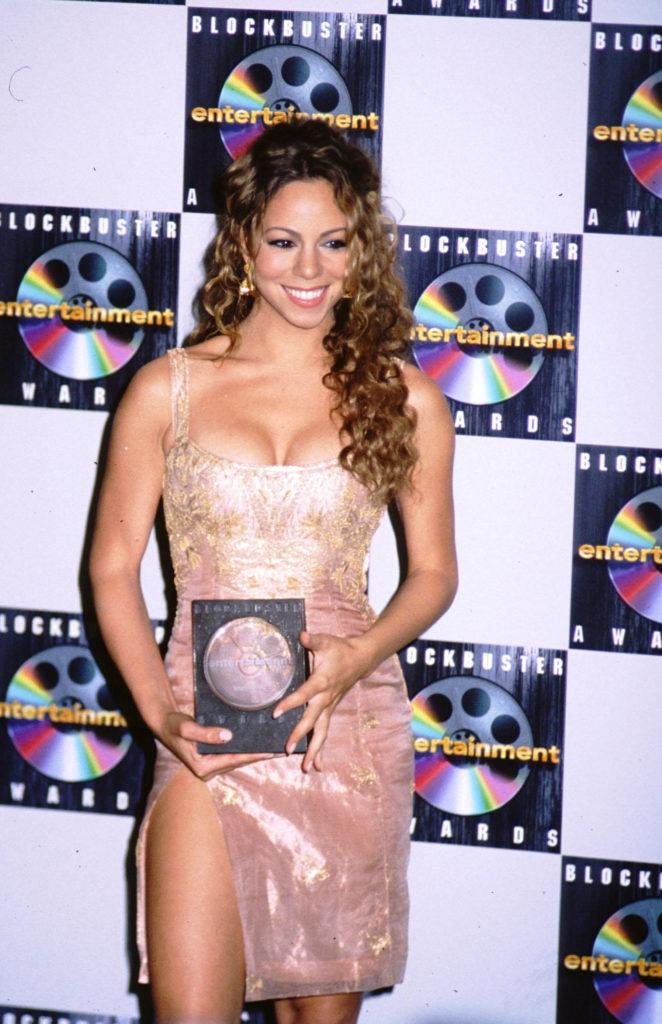 Mariah Carey with long dark blonde highlighted naturally curly half-up, half-down hairstyle wearing a pink and gold party dress.