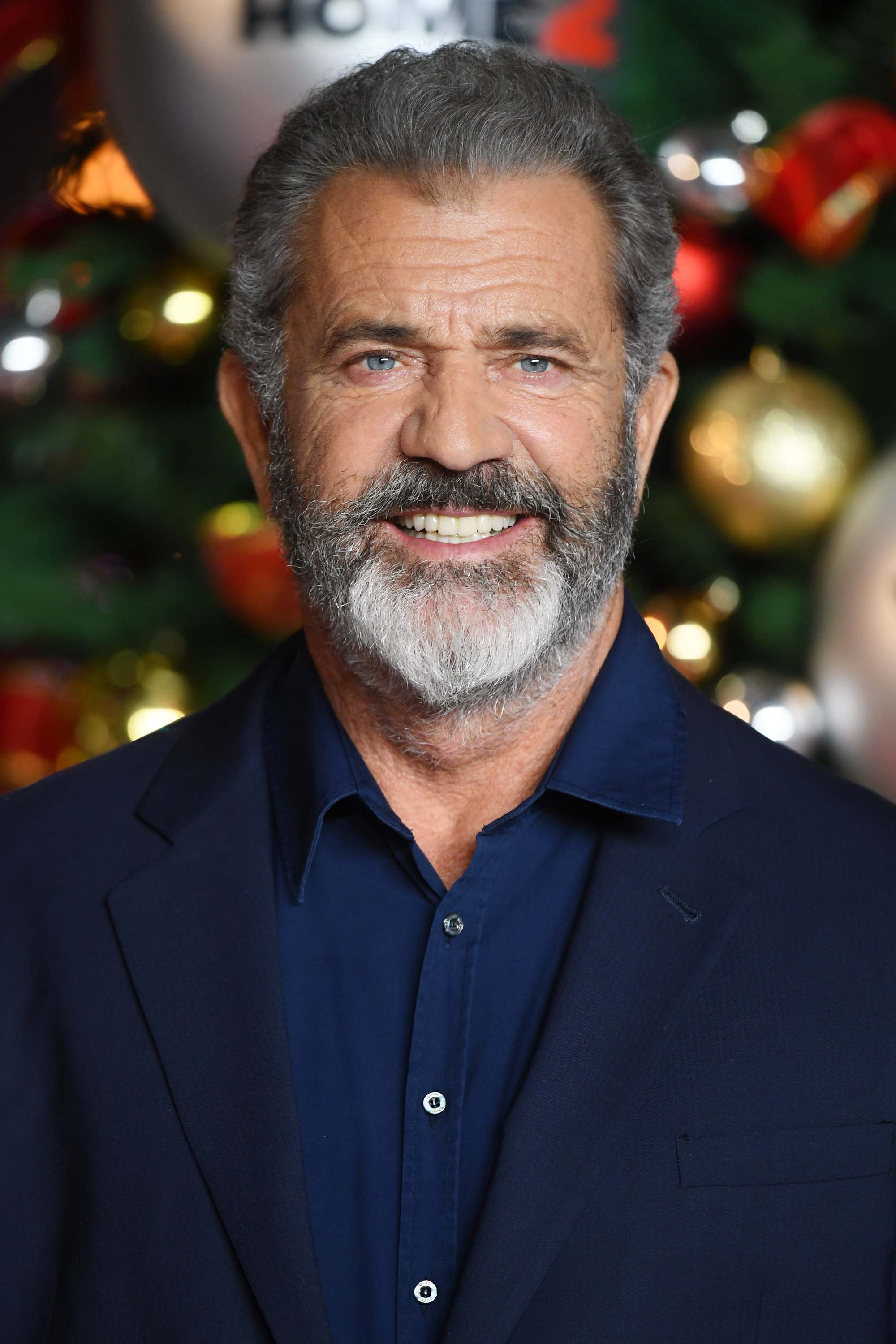 Hairstyles for men over 50: Mel Gibson with salt and pepper hair and full beard wearing a relaxed suit in front of a christmas tree.