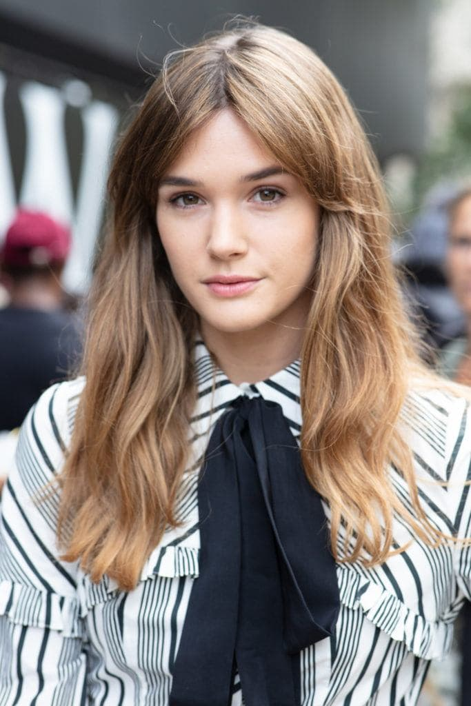 Sai Bennett with light brown wavy hair with Bardot bangs