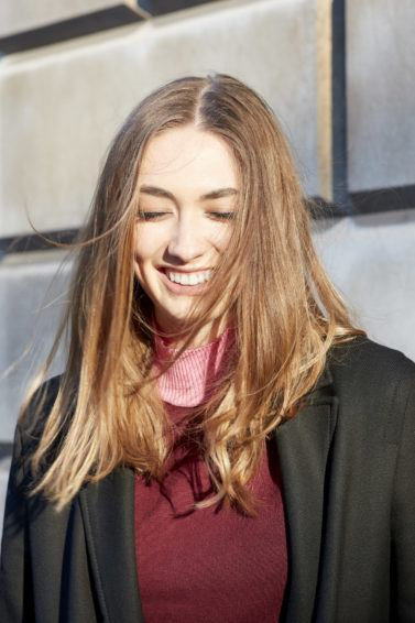 New year hair's resolutions: Shot of a woman swishing her healthy chestnut brown hair in the street, wearing maroon jumper with black jacket on the street all things hair uk