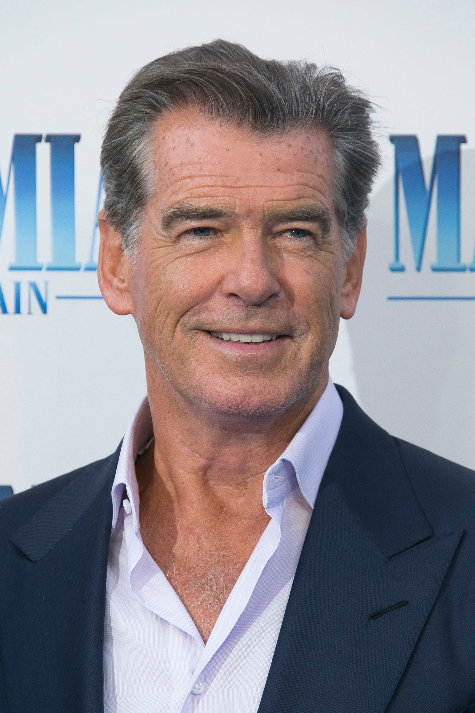Hairstyles for men over 50: Pierce Brosnan with grey short hair swept back wearing a relaxed blue suit at Mamma Mia premiere.