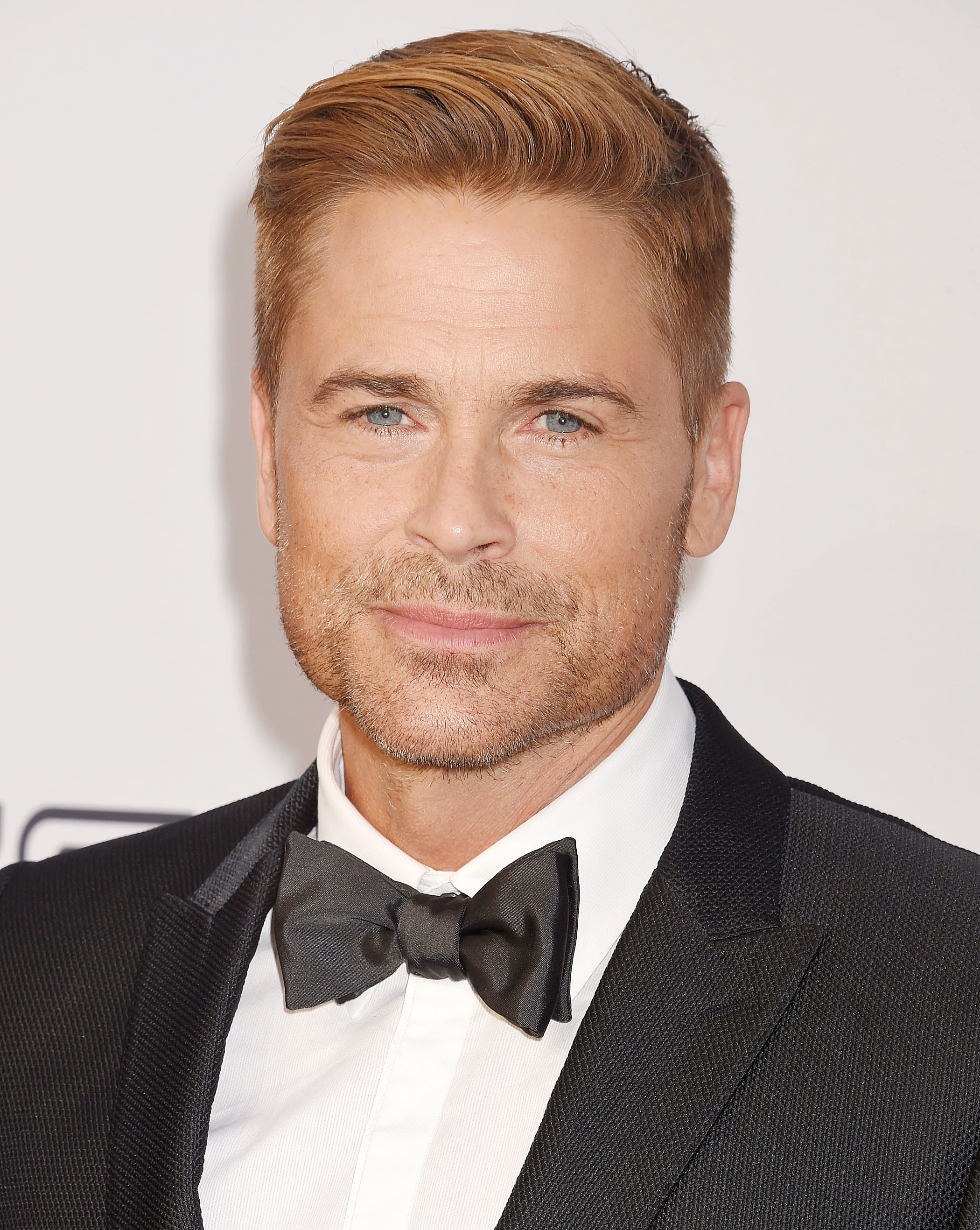 Hairstyles for men over 50: Rob Lowe with blonde short hair in tapered finish with soft combover wearing a smart suit.