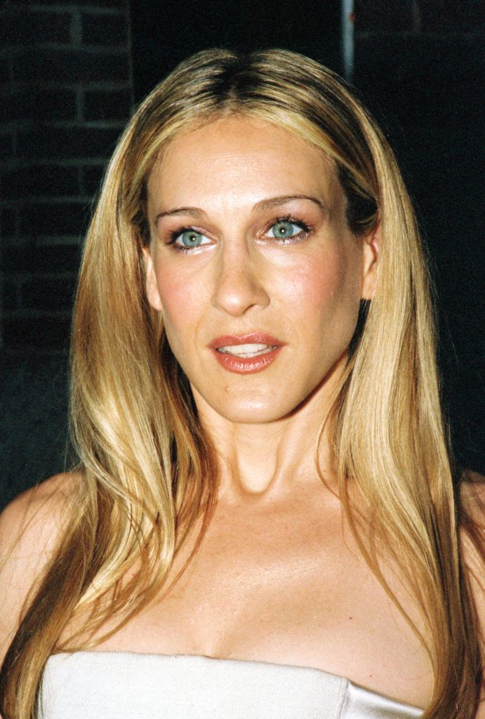 Sarah Jessica Parker with straight long blonde highlighted hair tucked behind her ears wearing a strapless dress.