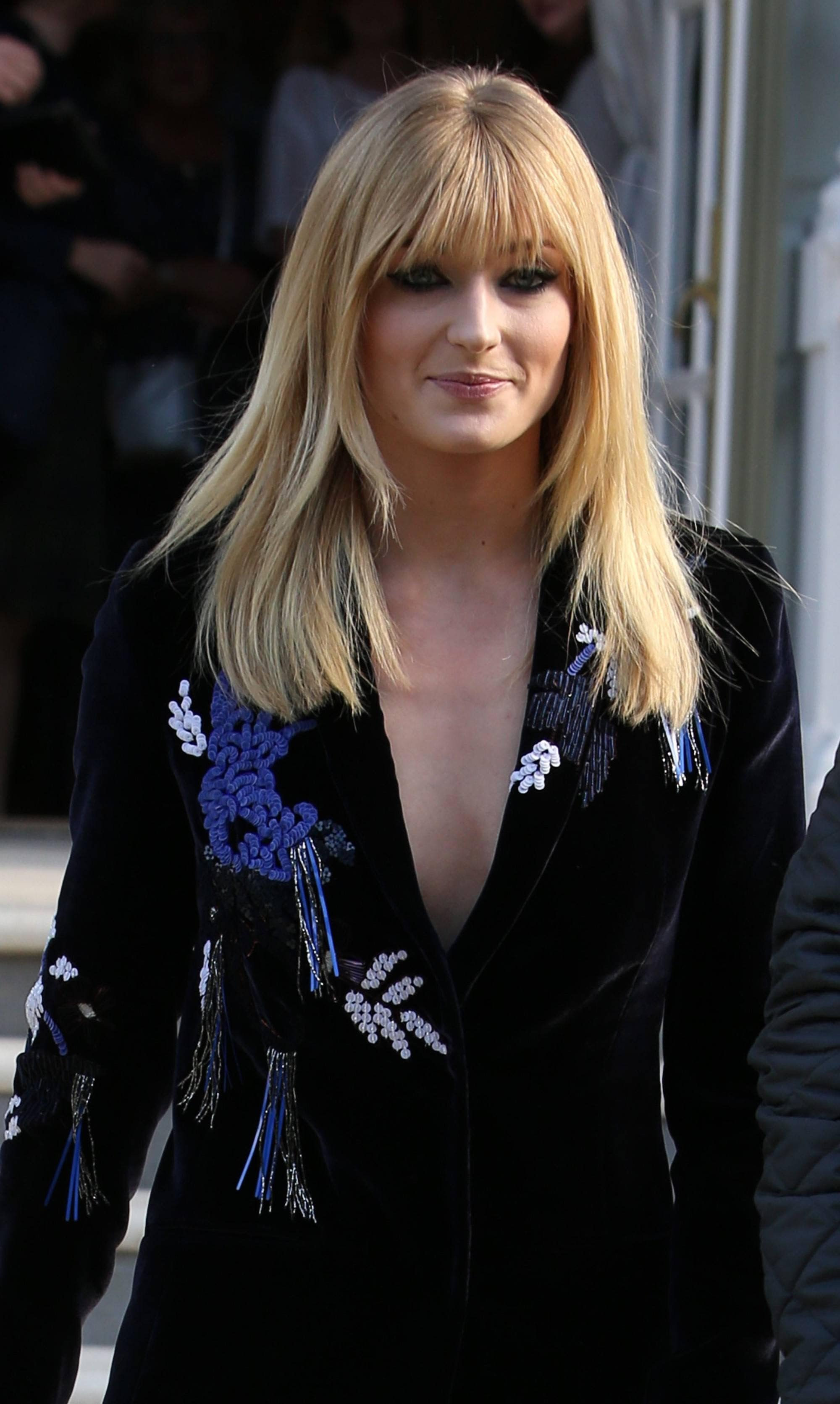 Sophie Turner with shoulder length layered hair with a fringe