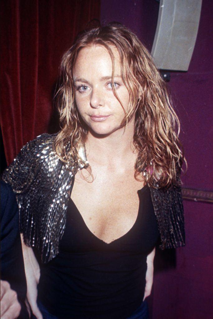 Stella McCartney with dark blonde wet look beach wave sin the '90s wearing a black v neck top.