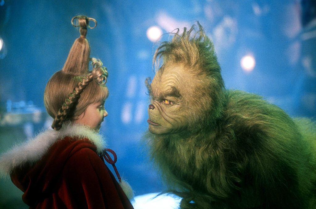The Grinch: Taylor Momsen as Cindy Lou Who with her hair golden blonde hair styled into a milkmaid braid, wearing red christmas outfit on set