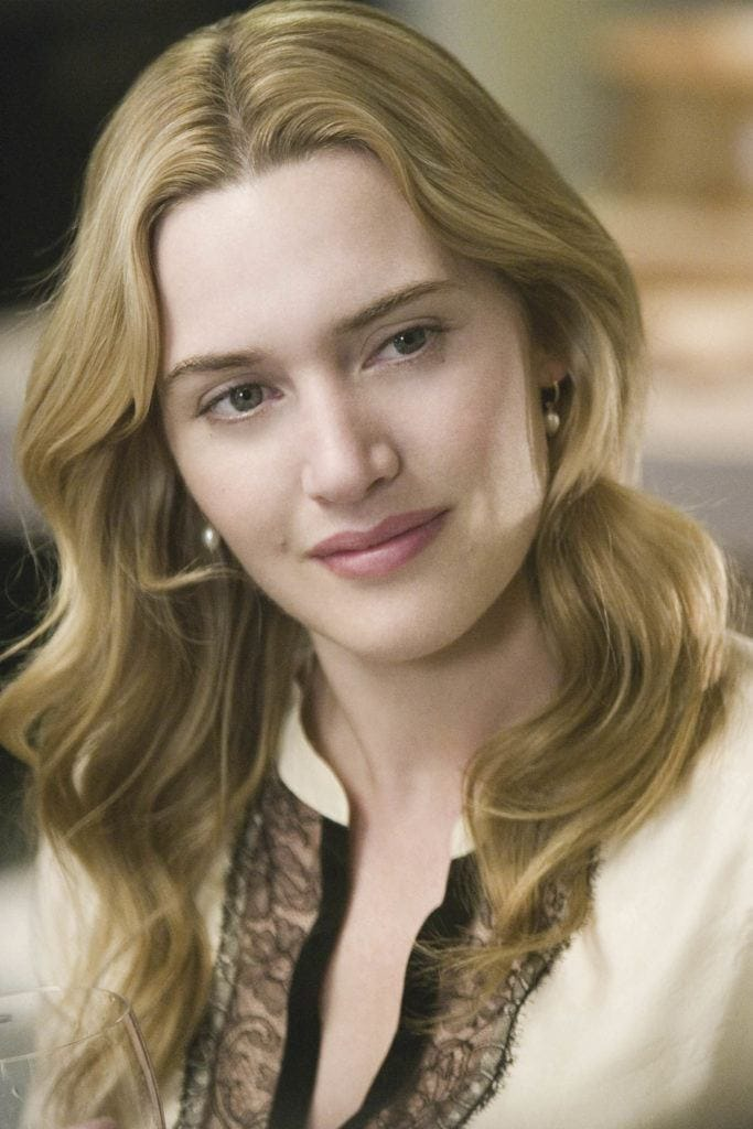 The Holiday: Kate Winslet as Iris, with golden blonde medium length hair styled into loose Hollywood waves, wearing white top and smiling on set