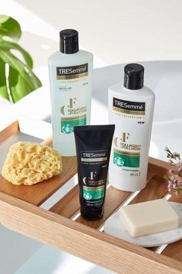Photo of a bath shelf, with the TRESemmé Collagen+ Fullness range on it, along with a loofa and a bar of soap.