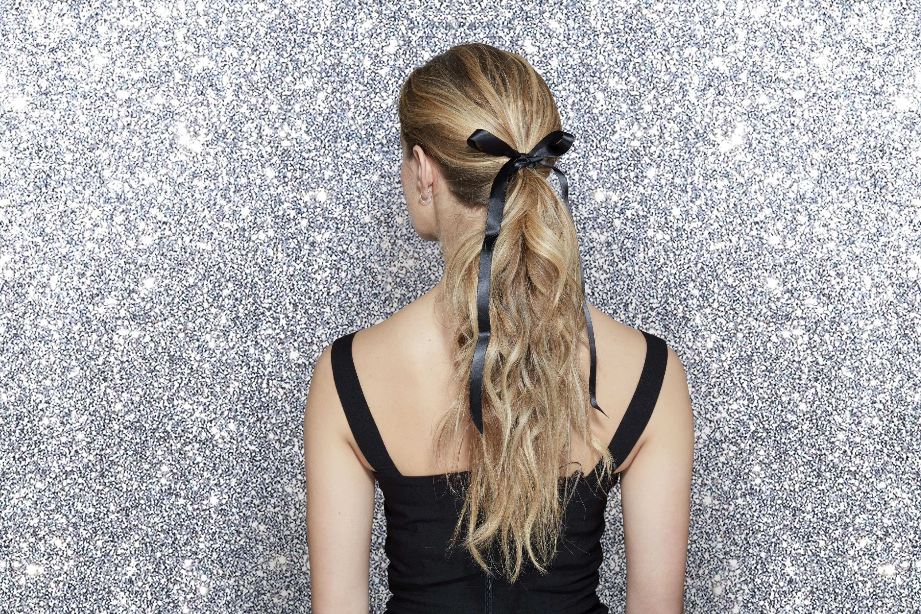 Back view of a blonde woman with long curly hair in a ponytail tied with a black ribbon, wearing a black dress and standing in front of a silver glitter background