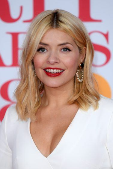 Holly Willoughby hair gallery: Woman with shoulder length blonde hair with soft wave wearing a white dress and red lipstick at awards event.