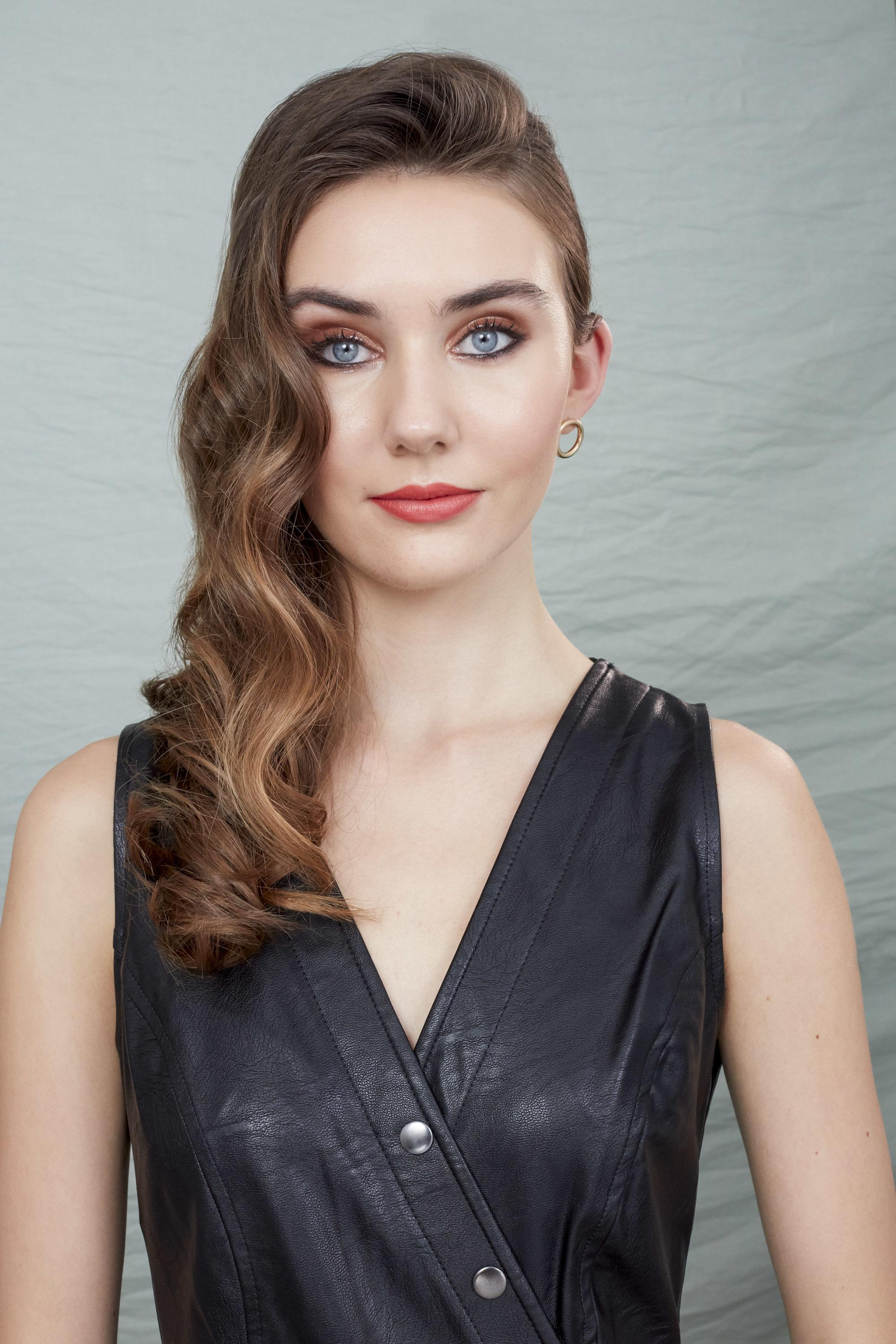 Brunette model with side-swept Hollywood glam waves, wearing a black leather dress