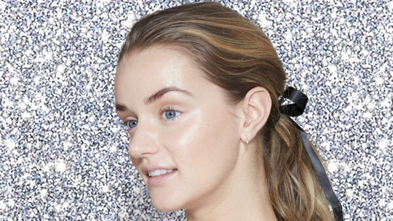 Blonde model with her hair tied back in a curly ponytail tied with a black ribbon, wearing a nude and black bodycon dress and standing in front of a silver glitter backdrop