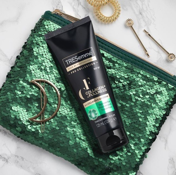 Close-up flatlay of the TRESemmé Collagen+ Fullness Thickening Balm on a green sequin clutch bag, with a gold moon shaped hair clip, hair slides and gold invisibobbles on a marble background