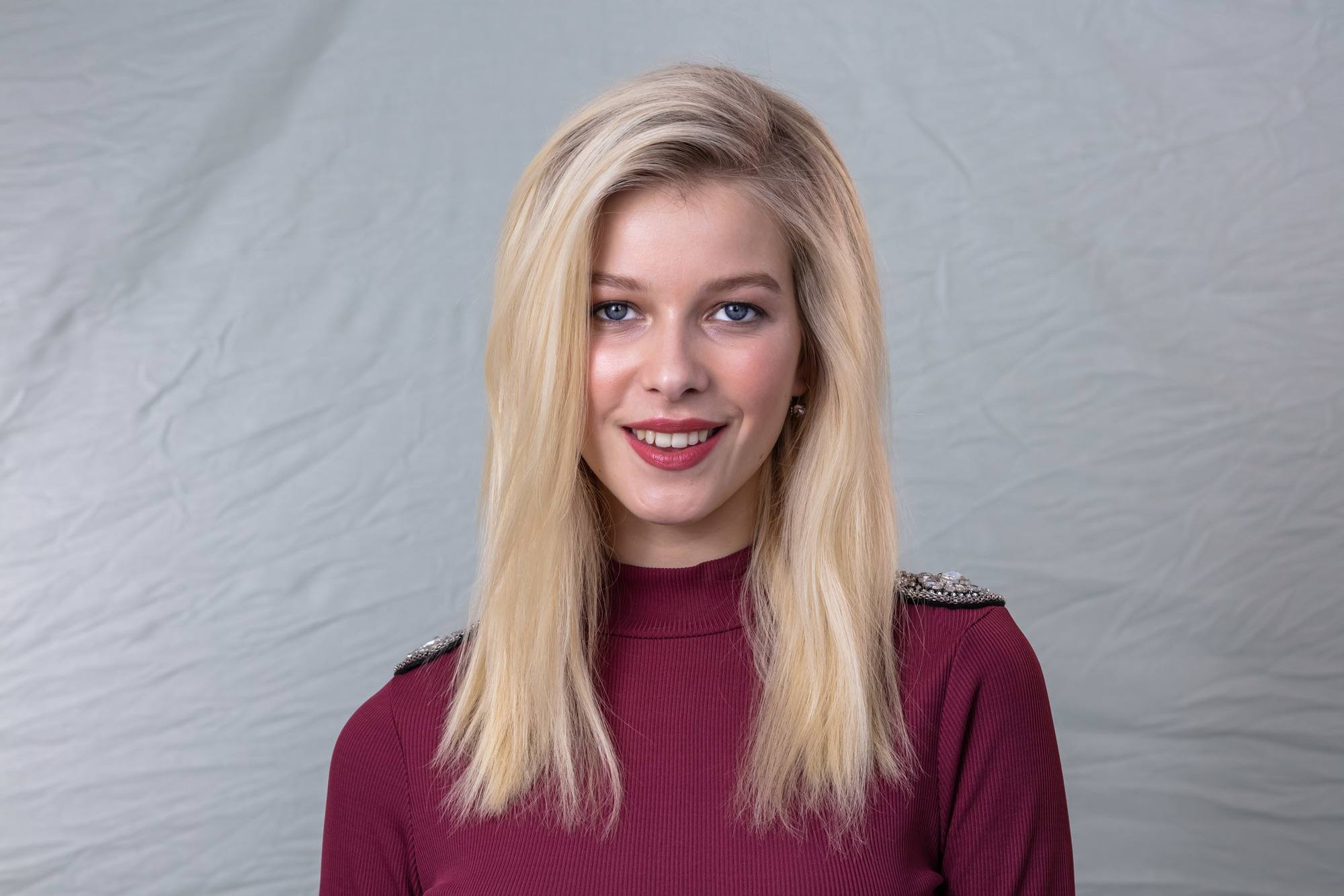 Volume hair: Landscape shot of a blonde model with straight mid-length hair, parted in a side parting, wearing a maroon high neck top