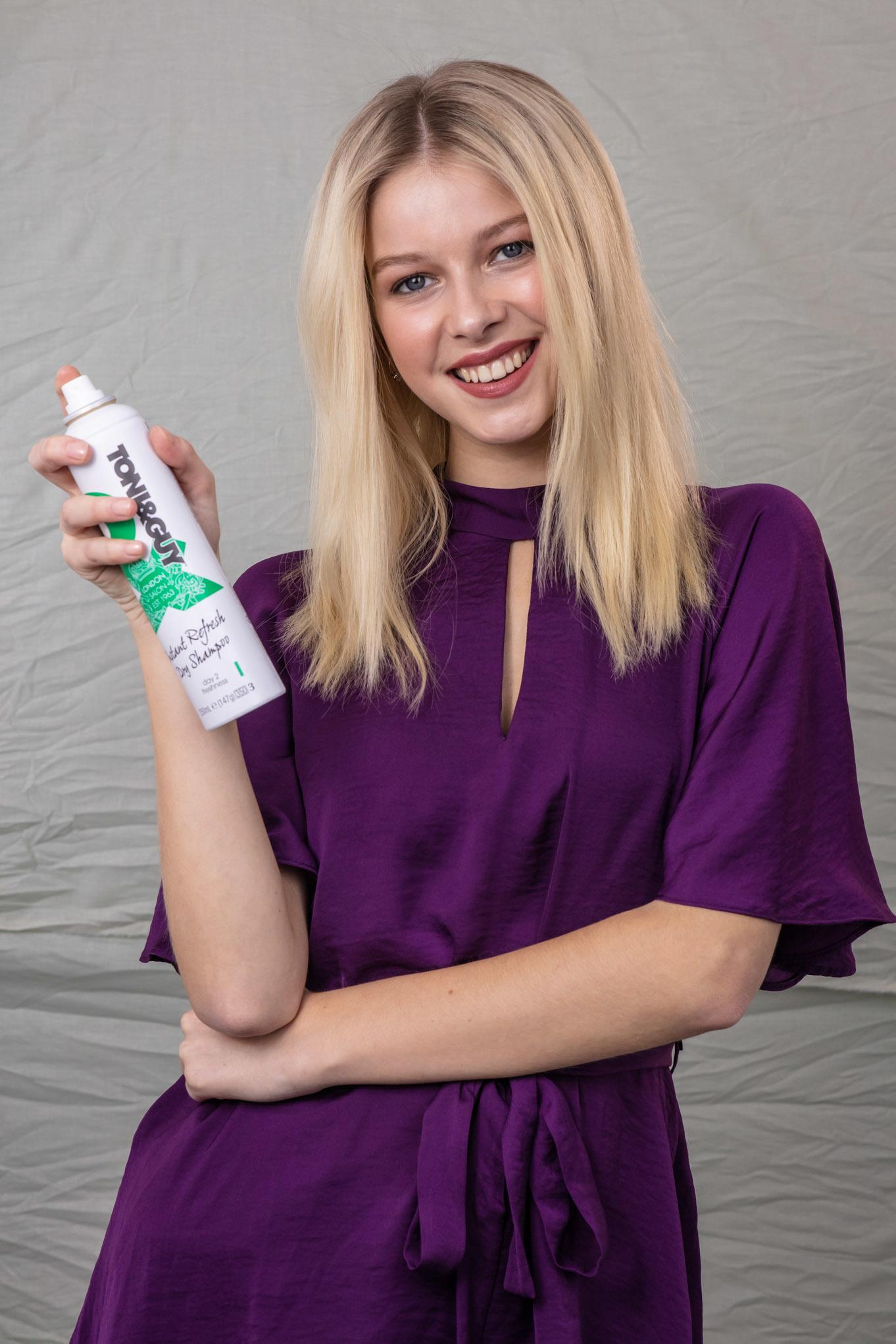Volume hair: Blonde model with straight, shoulder-length hair, holding a TONI&GUY Dry Shampoo, wearing a purple floaty top